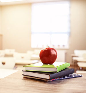 Stack of books with apple on top in welcoming classroom