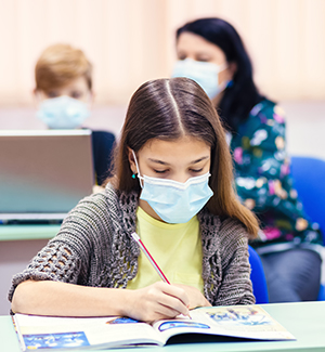 Student wearing face mask while sitting at desk in classroom