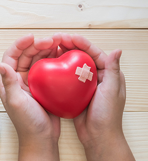 Adult hands holding a heart-shaped stone with a bandaid