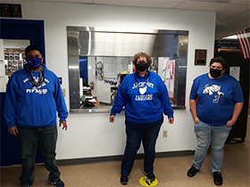 Three staff members posing for a picture wearing face masks