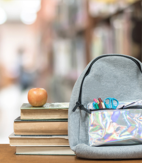 Backpack on table in front of books