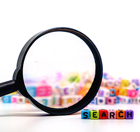 Magnifying glass next to SEARCH spelled out with blocks