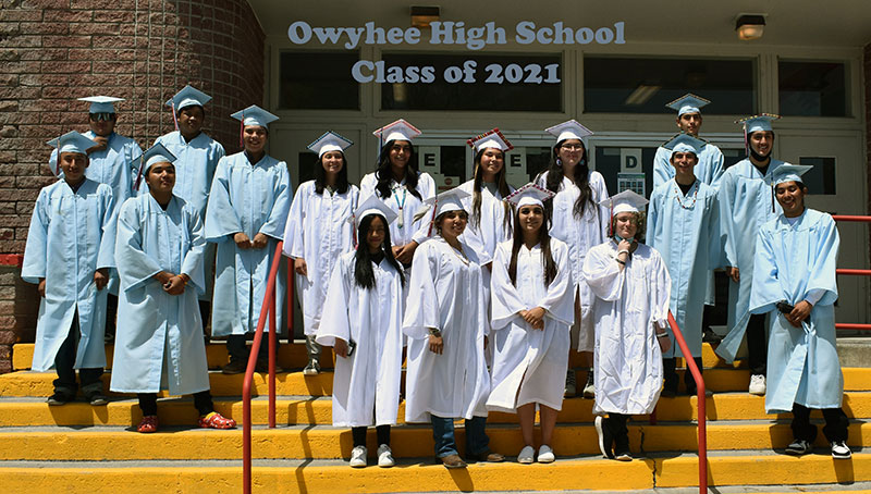 Graduating class of 2021 posing in front of the school entrance