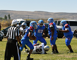 Football team playing against Pyramid Lake with referee