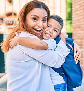 Happy student hugging teacher outside
