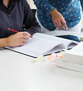 Tutor helping a student at a desk