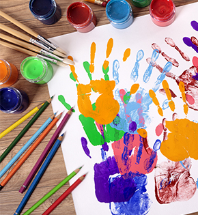 Colored pencils next to painted hand prints