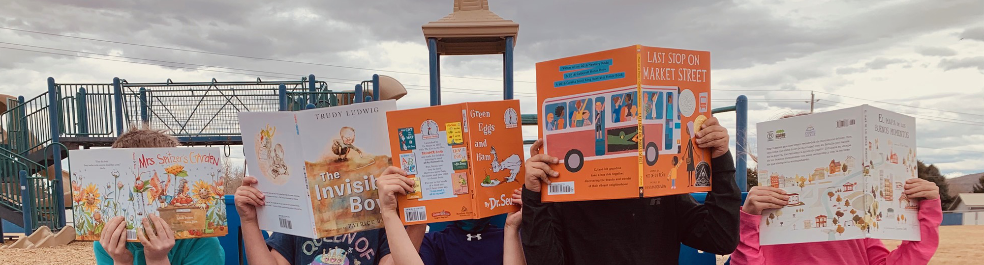 Students reading books by a playground