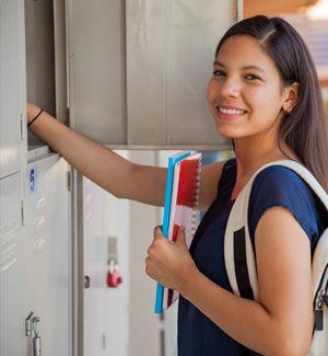 smiling student standing at locker
