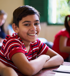 young boy in red shirt smiling while sitting in classroom