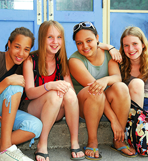 four female students sitting on steps smiling