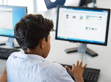 Boy search on desktop computer