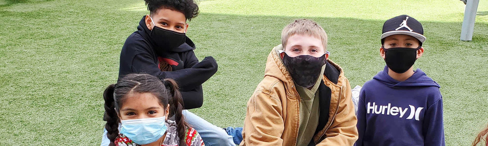 Four students outside wearing face masks