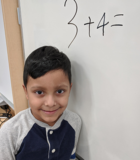 young student in front of board with math problem