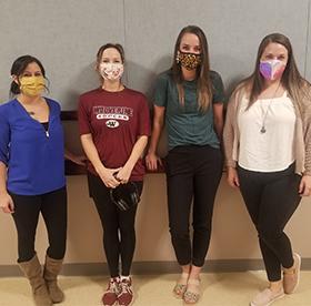 Teachers in the hallway wearing face masks