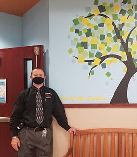 School teacher welcoming students in the hallway