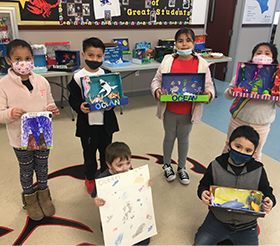 Group of elementary students posing with their science box projects