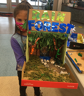 Little girl holding up her Rain Forest project