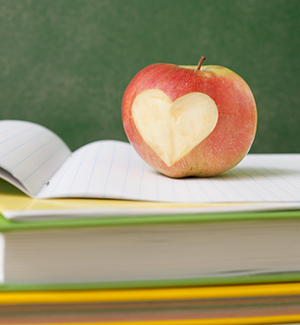 apple with heart-shaped bite sitting on top of books