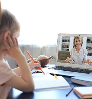 Teacher helping a student through an online connection on a laptop
