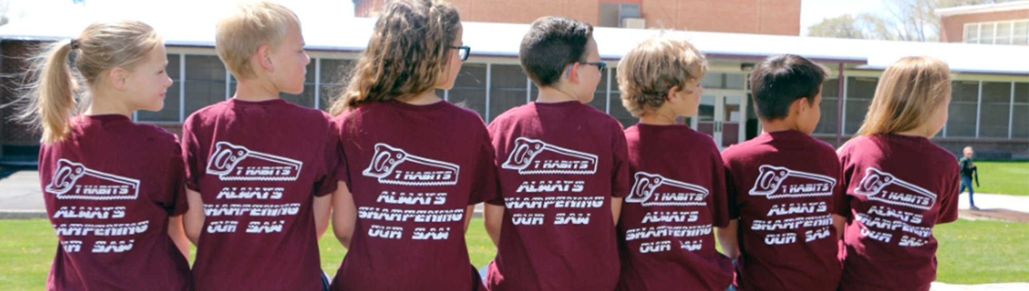 Group of happy Grammar students sitting outside in line wearing t-shirts with 7 Habits - Always Sharpening Our Saw