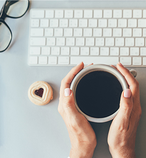 Parent holding a cup of coffee on a desk with a keyboard and cookie
