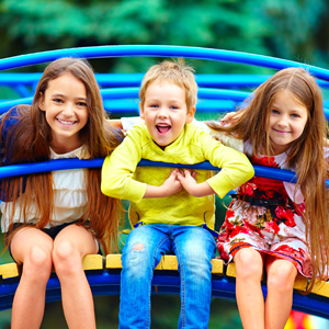 three students playing on jungle gym