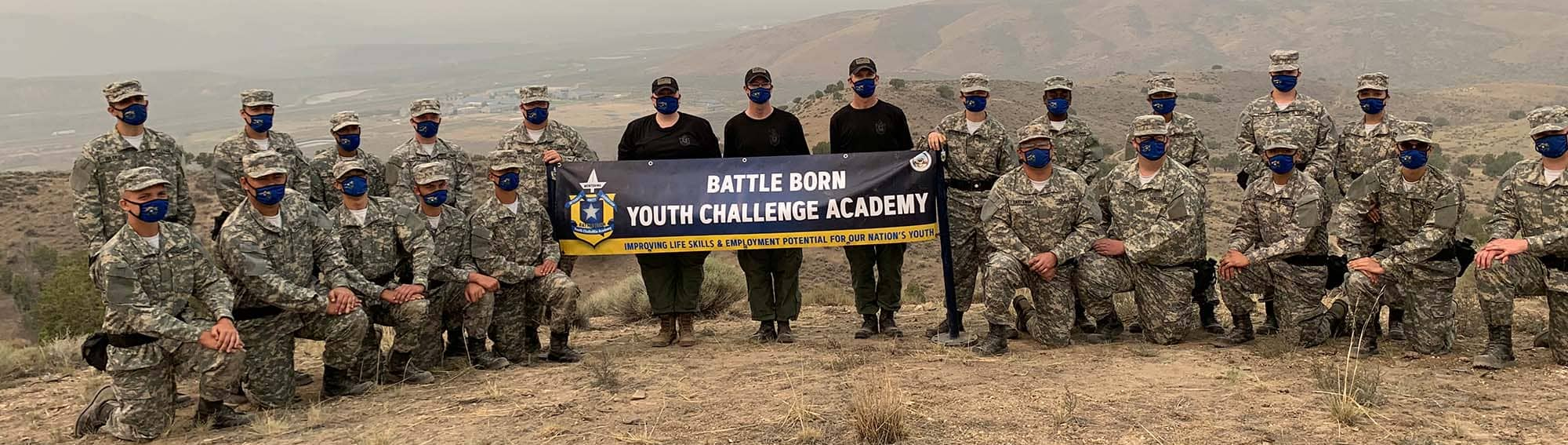 Students posing with Battle Born banner at the top of a mountain