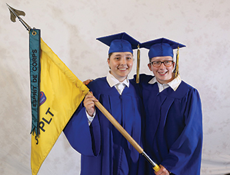 two students in graduation gowns holding a flag
