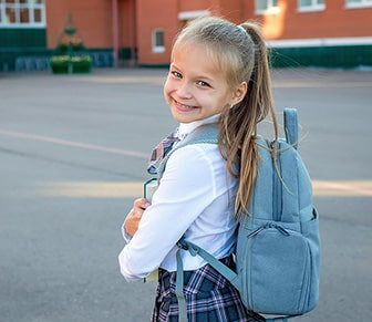 girl in a uniform and blue backpack smiling