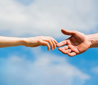 two hand reaching for one another with sky background