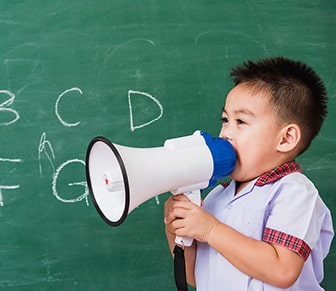 boy in front of chalkboard with megaphone