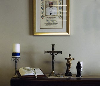 photo of priest on wall above table with rosary and cross statues