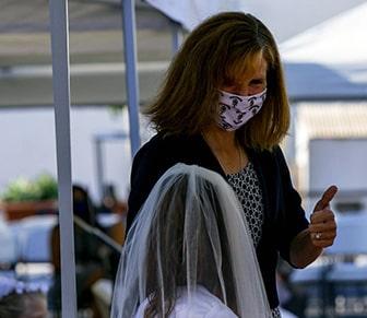 teacher wearing mask talking to student