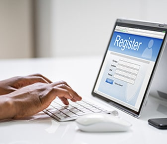hands typing on a laptop filling out an application