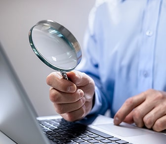 person holding a magnify glass by a laptop