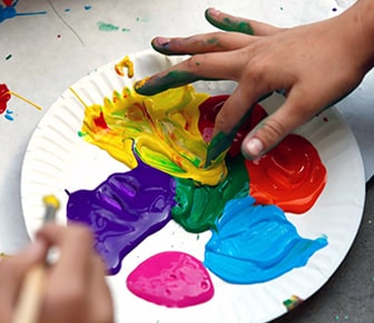 paper plate with finger paints and kid hands