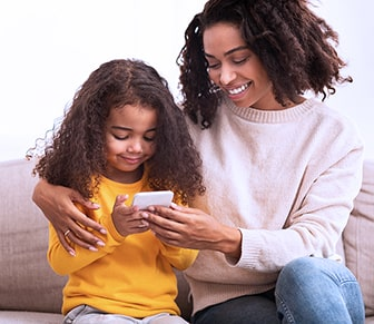 mother and daughter looking at a smartphone together