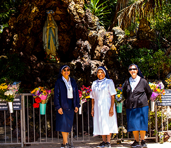 Three sisters in front of Virgin Mary statue