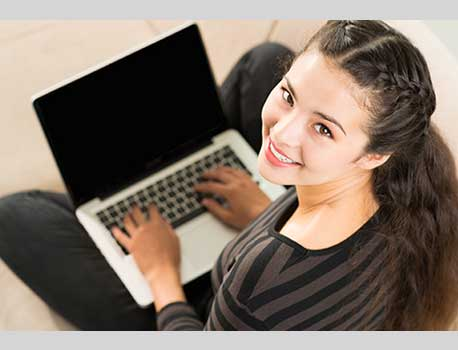 Smiling girl using a laptop