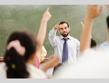 Teacher calling on students raising their hands in class