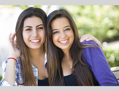 Two smiling girls posing together outside