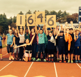 students holding up numbers on a track