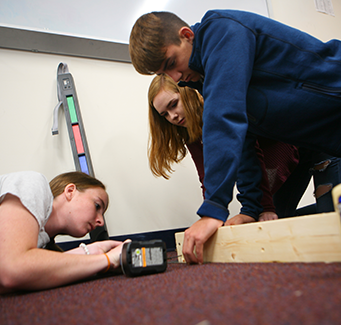 3 students working together on a wood project
