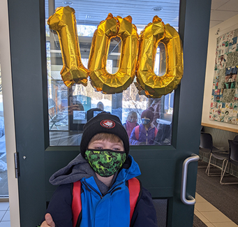 Student with number 100 balloons