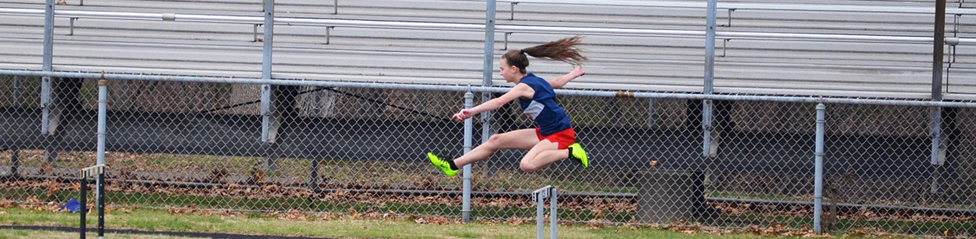 High school athlete practicing hurdles on the school track