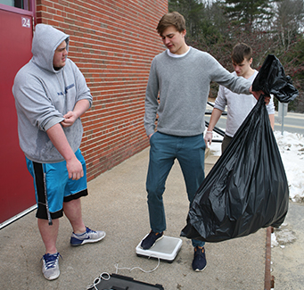 Two students outside weighing a big bag