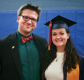Proud adult next to recent graduate