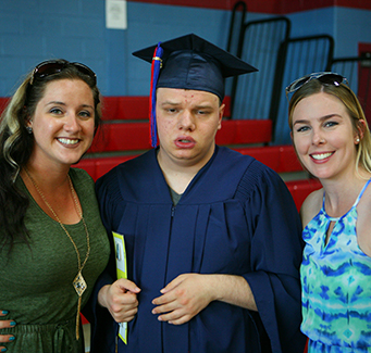 Two adults posing for a picture with a recent graduate