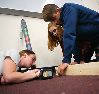 Three students building a wood project